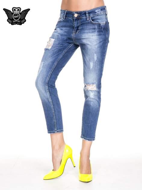 Ciemnoniebieskie spodnie jeansowe z dziurami podszytymi koronką