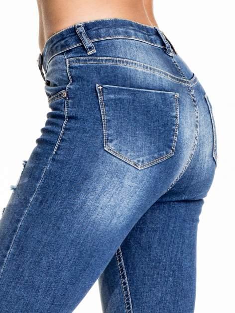 Ciemnoniebieskie spodnie skinny jeans z poszarpaną nogawką i dziurami                                  zdj.                                  6