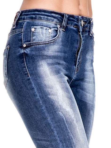Ciemnoniebieskie spodnie skinny jeans z przecieraną nogawką z przodu                                  zdj.                                  7