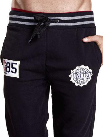 Czarne dresowe spodnie męskie z naszywkami i kieszeniami                                  zdj.                                  4