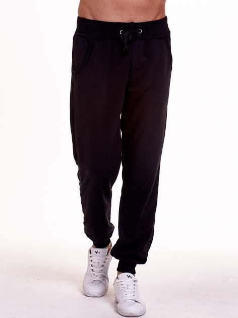 Czarne dresowe spodnie męskie z trokami w pasie i kieszeniami