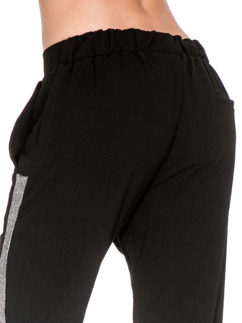 Czarne eleganckie spodnie dresowe z kontrastowym lampasem                                  zdj.                                  5