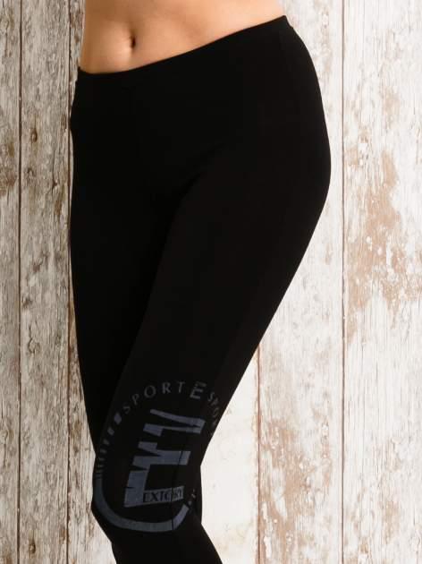 Czarne legginsy sportowe 3/4 z logo                                  zdj.                                  4