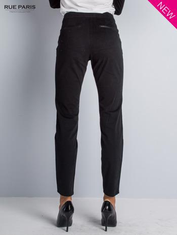Czarne spodnie cygaretki ze skórzaną lamówką przy kieszeniach