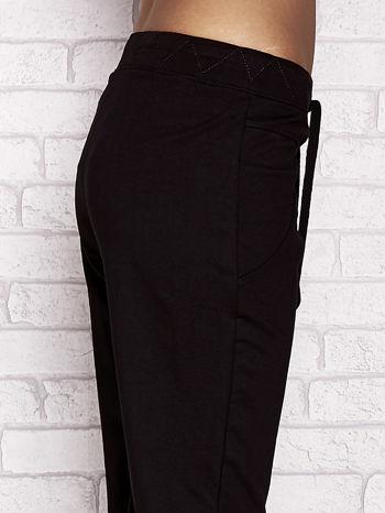 Czarne spodnie dresowe capri z ozdobnym przeszyciem w pasie                                  zdj.                                  5