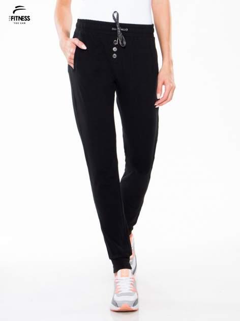 Czarne spodnie dresowe typu baggy z guzikami                                  zdj.                                  1