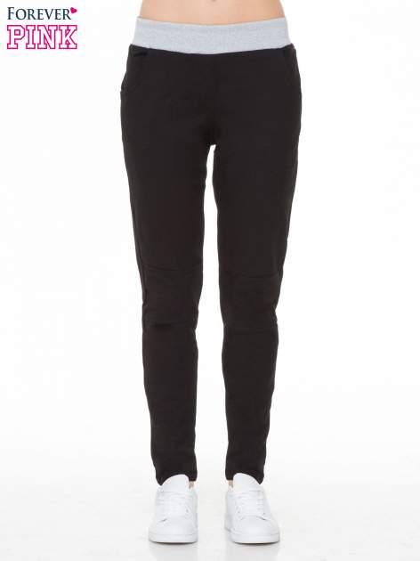 Czarne spodnie dresowe z guziczkami na nogawkach