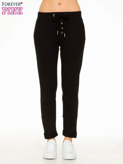 Czarne spodnie dresowe z guzikami wiązane w pasie