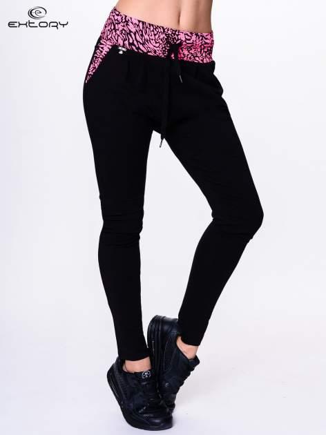 Czarne spodnie dresowe z koralowym pasem w panterkę