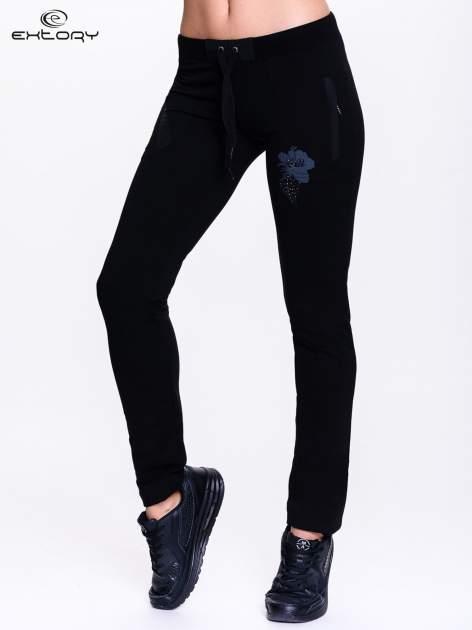Czarne spodnie dresowe z nadrukiem kwiatu z dżetami