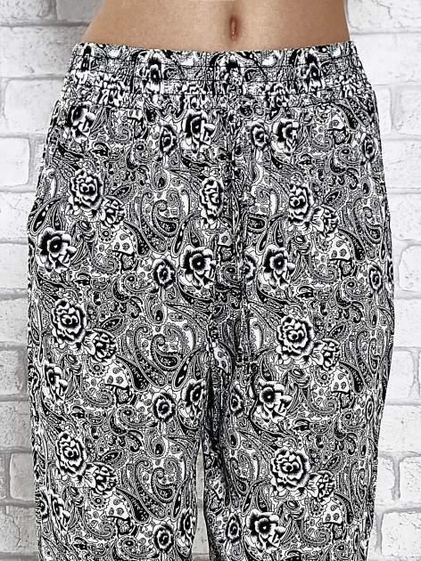Czarne zwiewne spodnie alladynki we wzór roślinny                                  zdj.                                  5