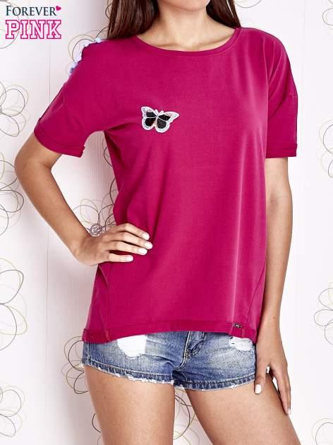 Fuksjowy t-shirt z naszywką motyla i pomponami                                  zdj.                                  1