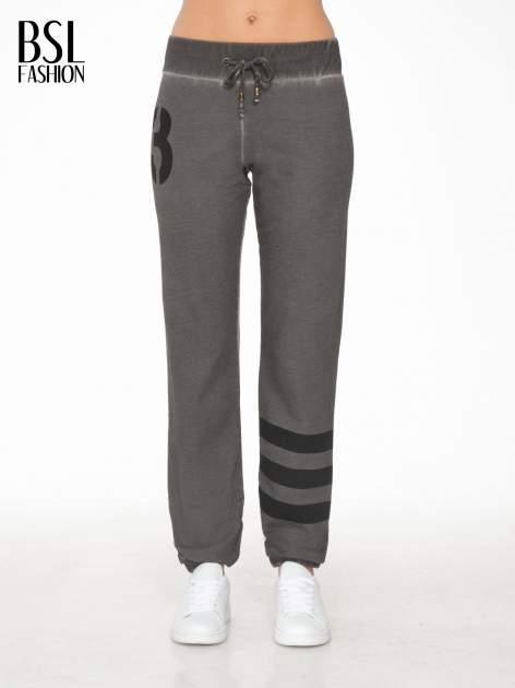 Grafitowe dresowe spodnie damskie z numerkiem i paskami na nogawkach                                  zdj.                                  1