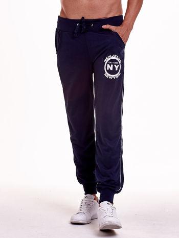 Granatowe dresowe spodnie męskie z lampasami po bokach i aplikacją