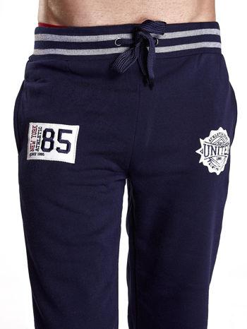 Granatowe dresowe spodnie męskie z naszywkami i kieszeniami                                  zdj.                                  4