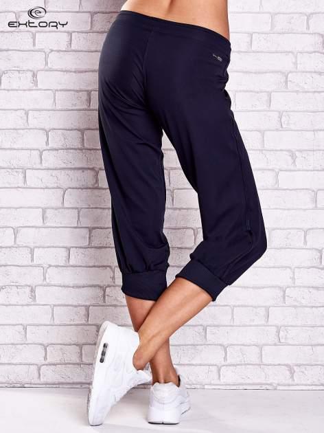Granatowe spodnie capri z aplikacjami z dżetów                                  zdj.                                  2