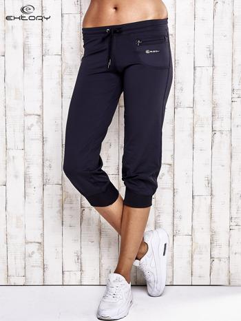 Granatowe spodnie capri z dżetami i kieszonką                                  zdj.                                  1