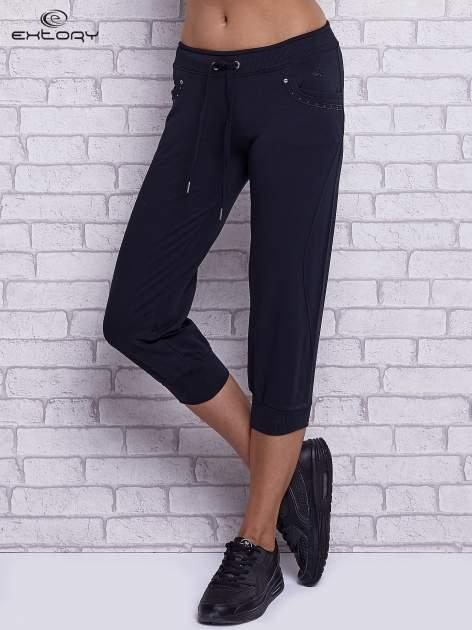 Granatowe spodnie capri z dżetami przy kieszeniach