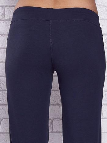 Granatowe spodnie capri z motywem pasków na nogawkach                                  zdj.                                  6
