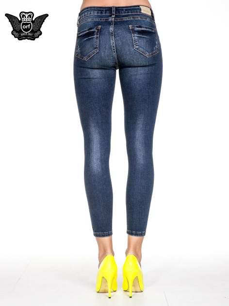 Granatowe spodnie skinny jeans z przecieraną nogawką z przodu                                  zdj.                                  5