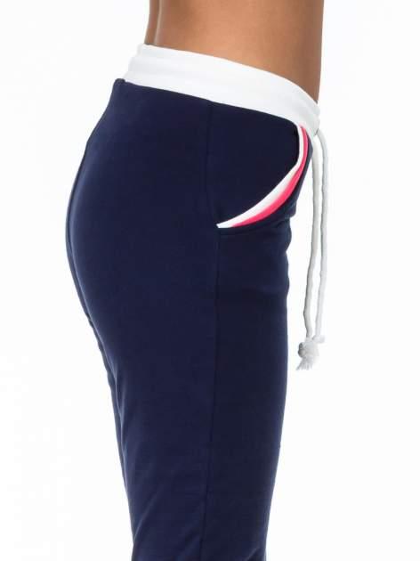 Granatowe spodnie z kolorowym akcentem przy kieszeniach                                  zdj.                                  6