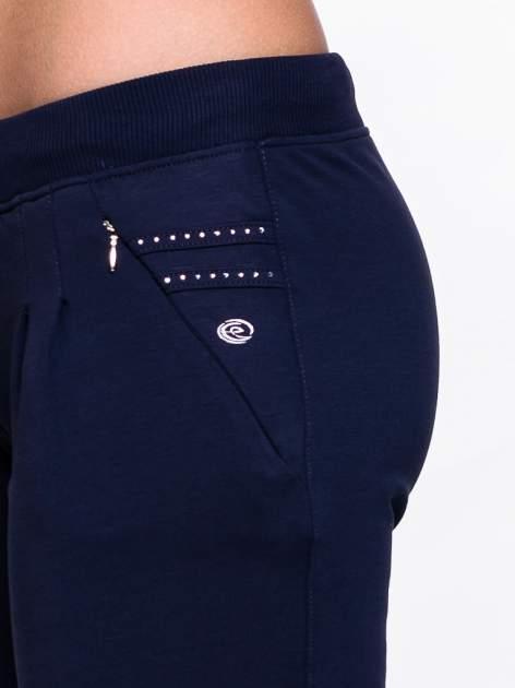 Jasnogranatowe spodnie dresowe z dżetami przy kieszeniach                                  zdj.                                  5