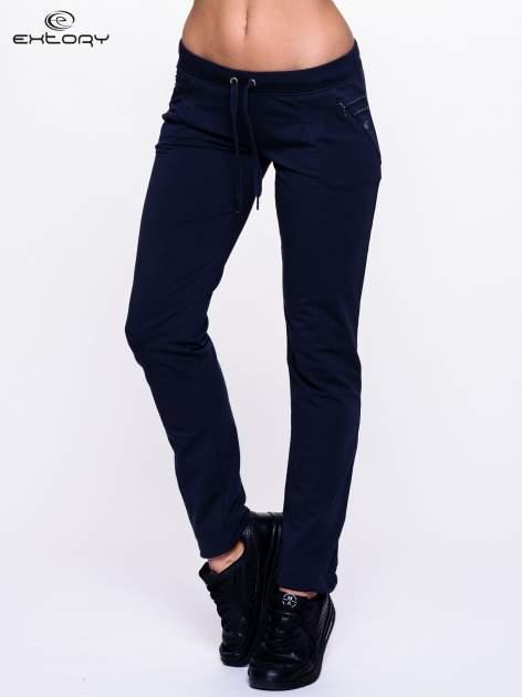 Jasnogranatowe spodnie dresowe z dżetami przy kieszeniach                                  zdj.                                  1