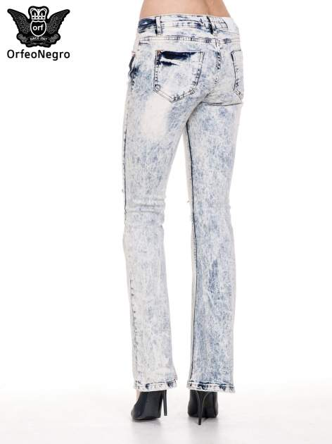 Jasnoniebieskie dekatyzowane spodnie jeansowe dzwony z przetarciami i dziurami