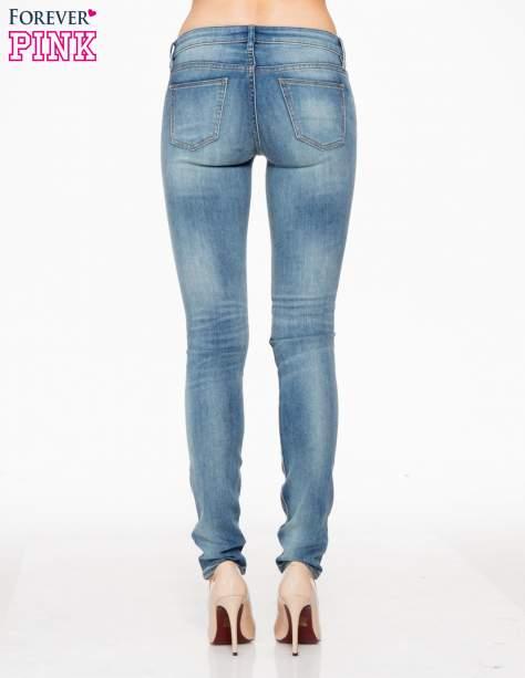 Jasnoniebieskie rozjaśniane spodnie jeansowe rurki                                   zdj.                                  4