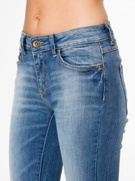 Jasnoniebieskie spodnie jeansowe rurki z przeszyciami na kieszeniach                                  zdj.                                  10