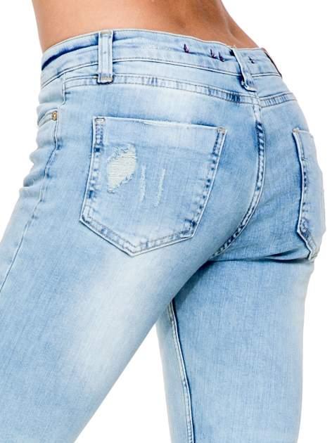 Jasnoniebieskie spodnie skinny jeans z rozdarciami na kolanie                                  zdj.                                  7