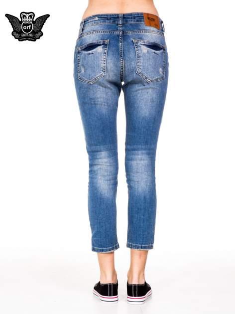 Niebieskie spodnie jeansowe rurki 7/8 z łatą i dziurami                                  zdj.                                  4