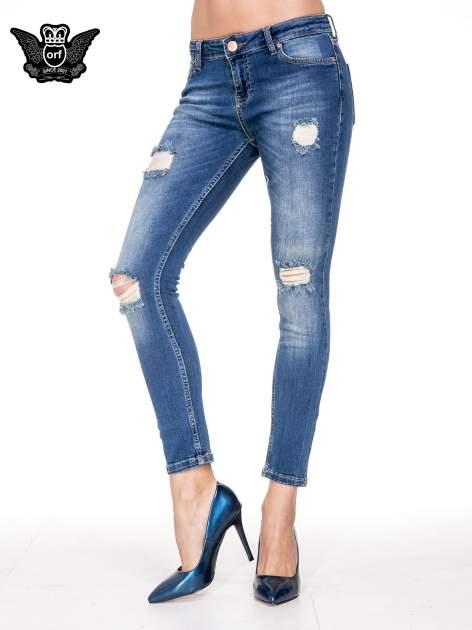 Niebieskie spodnie jeansowe rurki z dziurami i cieniowaniem