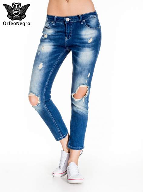 Niebieskie spodnie jeansowe rurki z dziurami na kolanach