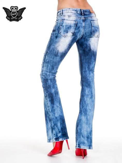 Niebieskie spodnie jeansowe rurki z rozjaśnianą i przecieraną nogawką                                  zdj.                                  4