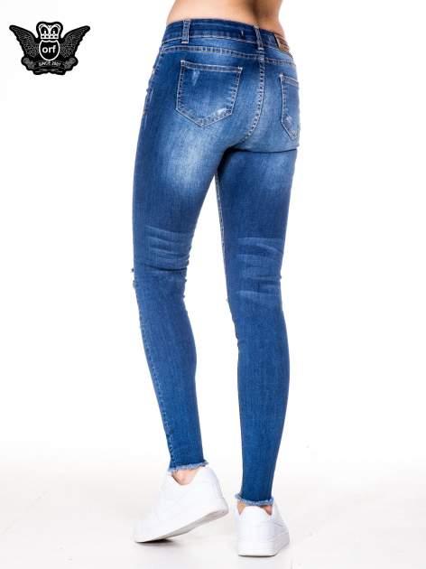 Niebieskie spodnie jeansowe rurki z rozjaśnianą nogawką i rozdarciami na kolanach                                  zdj.                                  4