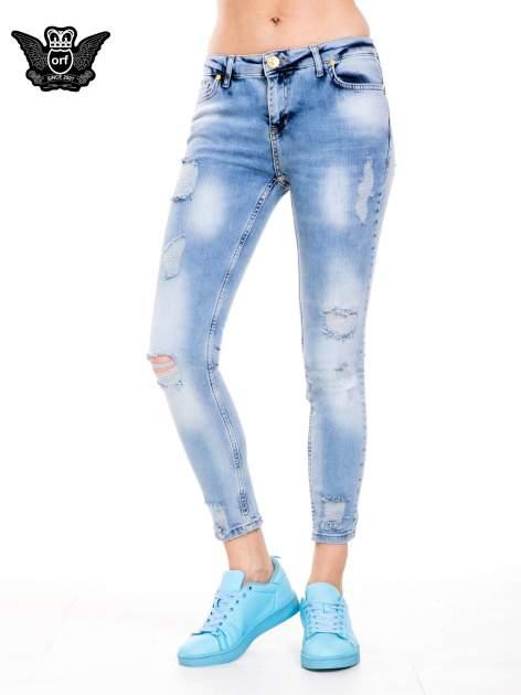 Niebieskie spodnie jeansowe z dziurami i rozdarciami                                  zdj.                                  1