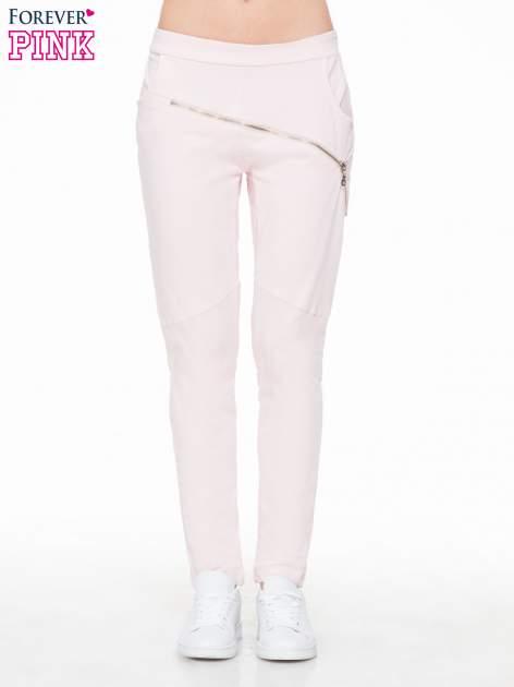 Różowe spodnie dresowe typu baggy z suwakiem