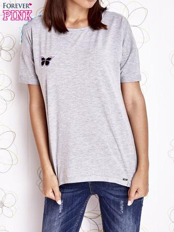 Szary t-shirt z naszywką motyla i pomponami