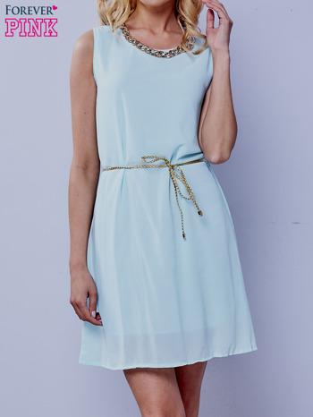 Turkusowa sukienka ze złotym łańcuszkiem przy dekolcie