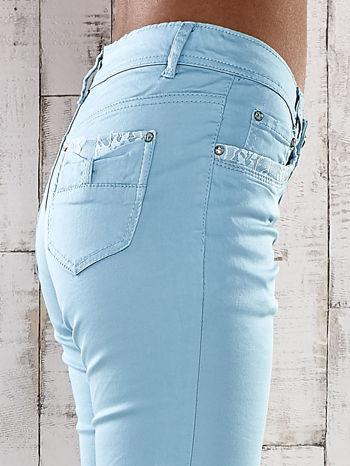 Turkusowe spodnie skinny jeans z koronką                                  zdj.                                  4