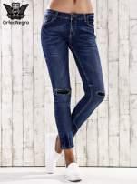 Ciemnoniebieskie spodnie jeansowe z łatami na kolanach