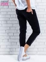 Czarne spodnie regular jeans z dżetami