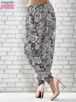 Czarne zwiewne spodnie alladynki we wzór kwiatowy                                  zdj.                                  2