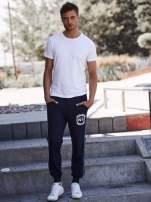 Granatowe dresowe spodnie męskie z lampasami po bokach i aplikacją                                  zdj.                                  2
