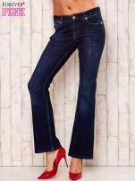Granatowe rozszerzane spodnie jeansowe                                   zdj.                                  1