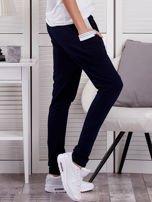 Granatowe spodnie dresowe ze ściągaczami przy kieszeniach                                  zdj.                                  5