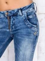 Niebieskie jeansowe spodnie rurki z przetarciami i haftami                                  zdj.                                  4