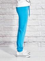 Turkusowe spodnie dresowe dla dziewczynki z letnim nadrukiem                                  zdj.                                  3